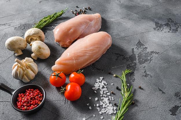 회색 배경에 원시 유기농 닭 가슴살입니다. 음식 준비, 텍스트에 대 한 측면보기 공간.