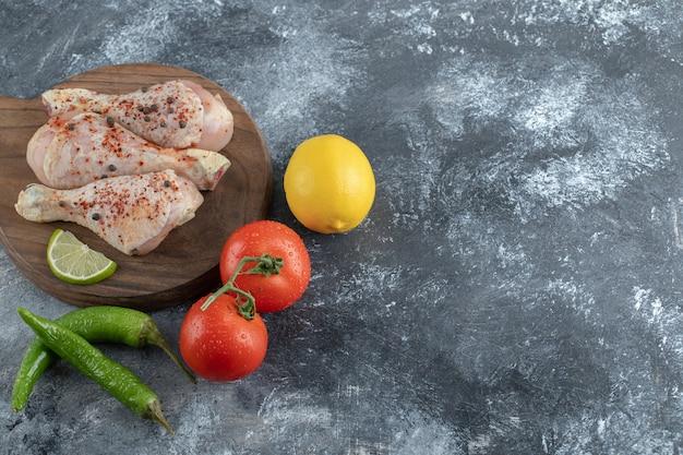 Cosce di pollo organiche crude con ingredienti per cucinare.