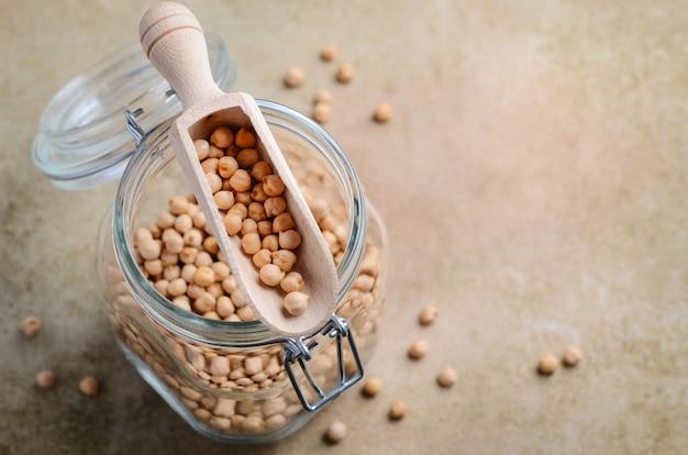 Raw organic chickpeas in a glass jar, healthy vegan vegetarian food ingredient.