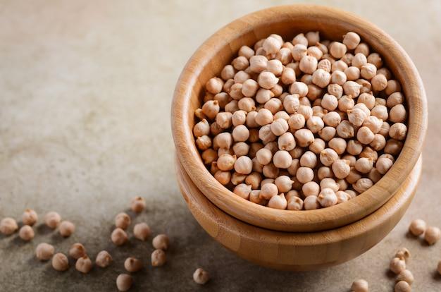木製ボウル、健康的なビーガンベジタリアンフード成分の生の有機ひよこ豆。