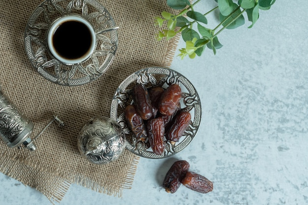 Raw organic dates on glass saucer with cup of coffee.