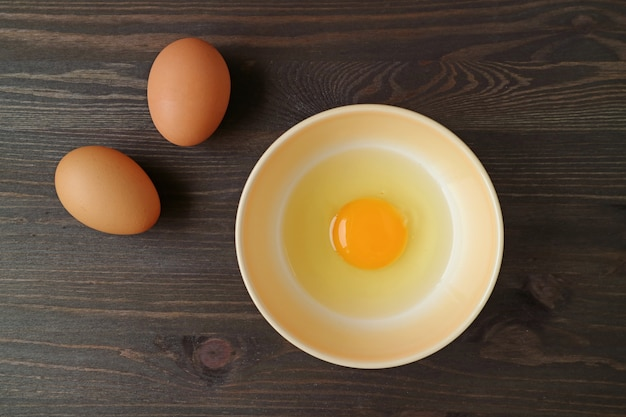 Raw organic egg in a bowl with two eggs on wooden table