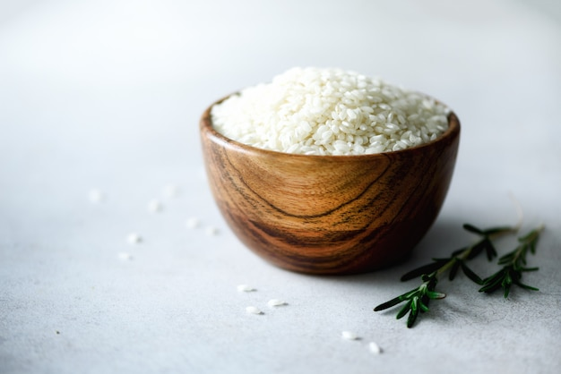 Raw organic jasmine rice in wooden bowl and rosemary on light concrete. food ingredients. copy space