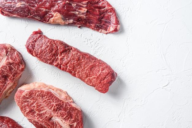 デンバーの近くの生の有機マチェーテステーキと白い背景の上のブレード霜降り牛