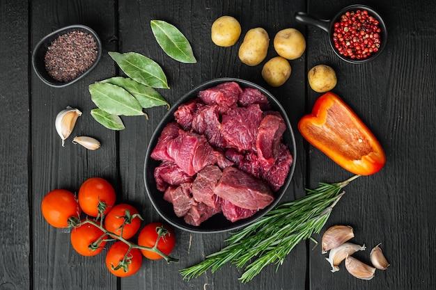 Сырое органическое мясо говядины или баранины и картофель, на черном деревянном