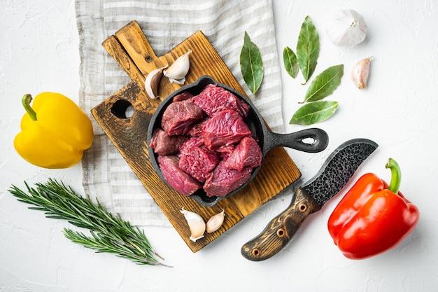 Сырое органическое мясо говядины или баранины со сладким перцем на чугунной сковороде на белой каменной поверхности