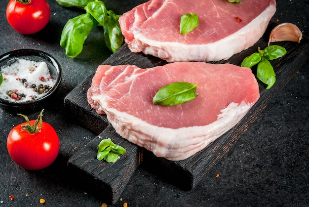 Raw organic meat. pork steaks, fillets for grilling, baking or frying. on a wooden cutting board, with salt, pepper, basil, tomatoes, garlic. on a gray stone table.