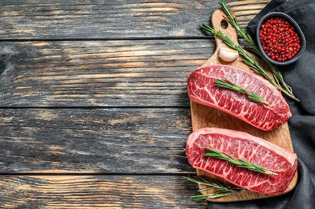 Сырое органическое мясо стейк из устрицы твагю. черный деревянный фон. вид сверху. скопируйте пространство.