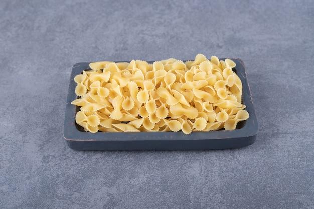 Raw organic pasta on dark board.