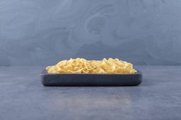 Pasta organica cruda sul bordo scuro.