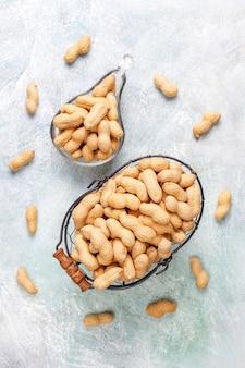 Сырой органический арахис в скорлупе.