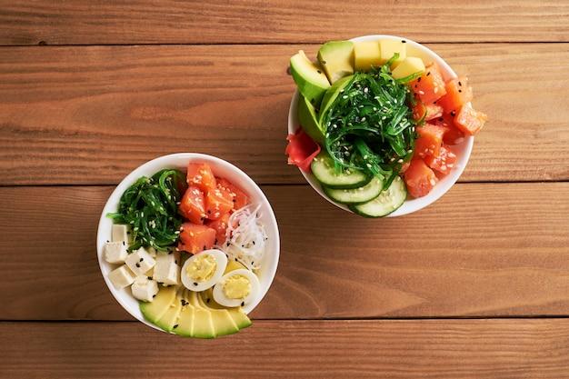 Raw organic poke bowl with with rice, avocado, salmon, mango, cucumbers, sweet onions two plates
