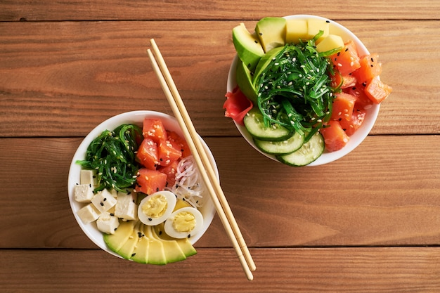 Raw organic poke bowl with with rice, avocado, salmon, on wooden background top view