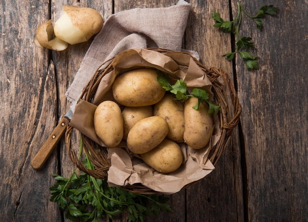 Raw organic potato with parsley  in basket on wooden table top view