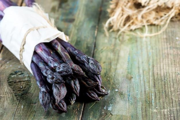 生の有機紫アスパラガスの槍は木製の背景に健康的なダイエット食品を調理する準備ができています。