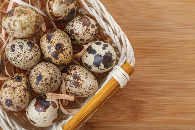 Raw organic quail eggs in bamboo basket on wooden table.