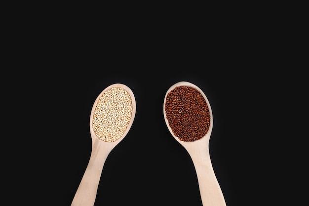 Сырые органические красные и белые зерна киноа в деревянных ложках на черном фоне