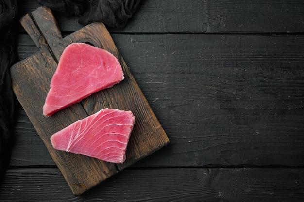 Сырое органическое филе тунца. набор морепродуктов, на деревянной разделочной доске, на черном деревянном