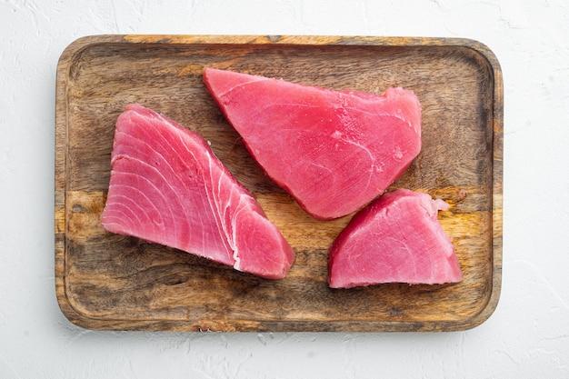 Сырое органическое филе тунца. набор морепродуктов, на деревянном подносе, на белом камне