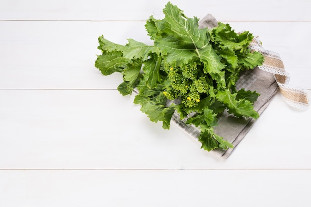 Raw organic turnip greens ready to eat on a white wooden background with copy space