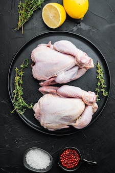 黒の背景、上面図にハーブスパイス成分を含む生の有機未調理の丸ごとの鶏肉