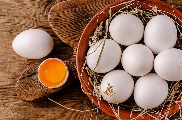 木製のテーブルに生の有機白い卵。上面図