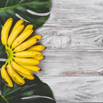 白い木製の表面の上面図に束の生の有機黄色の赤ちゃんバナナ
