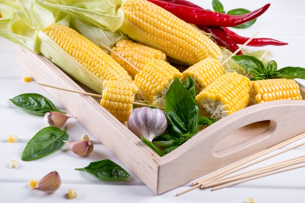 Raw organic yellow corn on the cob ready to grill with hot chili pepper garlic and herbs. mexican corn. ideas for barbecue and grill parties