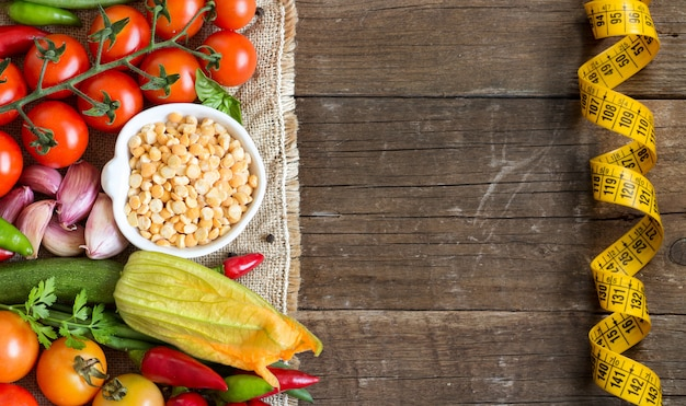 Raw organic  yellow peas in bowl and raw vegetables with measuring tape on wooden table top view with copy space