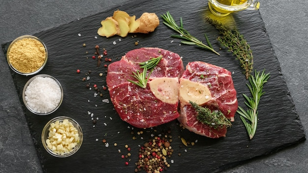Raw osso buco steak on a black stone surrounded by spices