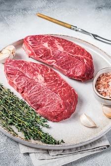 생 굴 탑 블레이드 또는 허브와 함께 접시에 플랫 아이언 로스트 비프 고기 스테이크. 흰 바탕. 평면도.