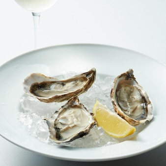 Raw oysters served on the half shell over ice with lemon in the white plate