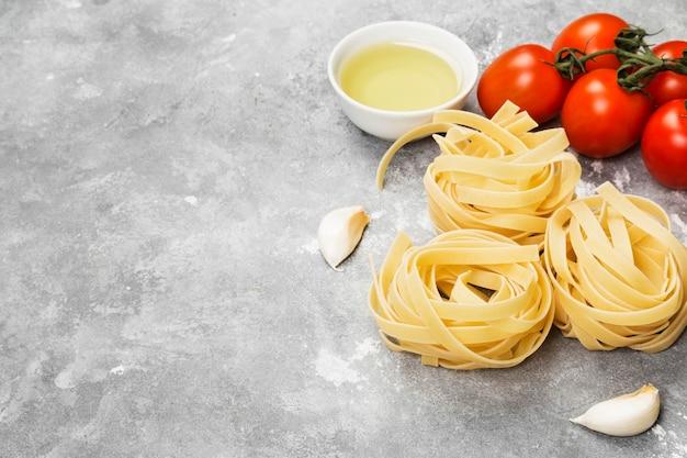Сырые макароны и ингредиенты для приготовления пищи (помидоры черри, оливковое масло, чеснок) на сером фоне. копировать пространство пищевой фон