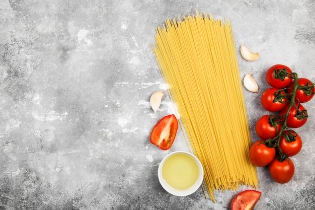 Сырые макароны и ингредиенты для приготовления пищи (помидоры черри, оливковое масло, чеснок) на сером фоне. вид сверху, скопируйте пространство. пищевой фон