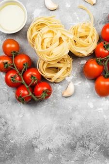 Сырые макароны и ингредиенты для приготовления пищи (помидоры, оливковое масло, чеснок) на сером фоне. вид сверху, скопируйте пространство. пищевой фон