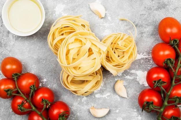 Сырые макароны и ингредиенты для приготовления пищи (помидоры, оливковое масло, чеснок) на сером фоне. вид сверху. пищевой фон