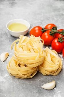 Сырые макароны и ингредиенты для приготовления пищи (помидоры, оливковое масло, чеснок) на сером фоне