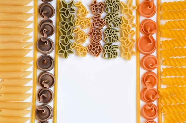 다양한 색상과 종류의 생 파스타와 스파게티가 세로로 놓여 있습니다