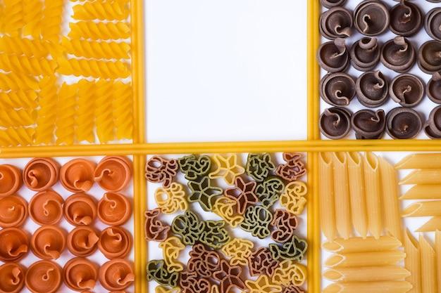 다양한 종류와 색상의 생 파스타와 스파게티가 다른 장소에 놓여 있습니다.