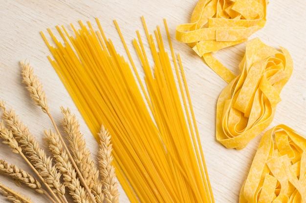 生パスタと小麦の小穂。健康的な炭水化物。