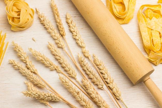 生パスタと小麦の小穂、めん棒。