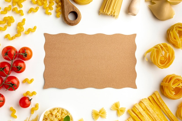 Raw pasta assortment and tomatoes with cardboard mock-up