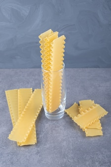 Raw pasta for baking lasagna on stone background.