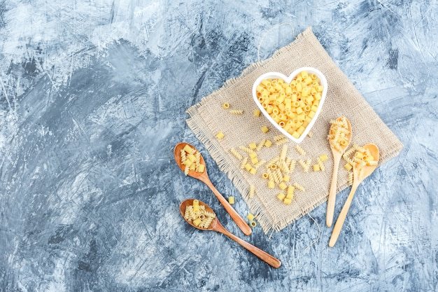 Raw pasta in bowl and wooden spoons on plaster and piece of sack background. top view.
