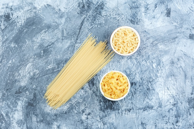 Raw pasta in bowls flat lay on a grungy plaster background