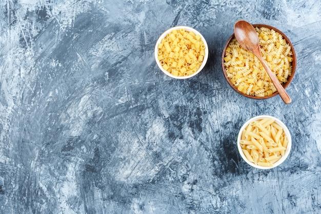 Pasta cruda in ciotole con vista dall'alto cucchiaio di legno su uno sfondo di intonaco grigio
