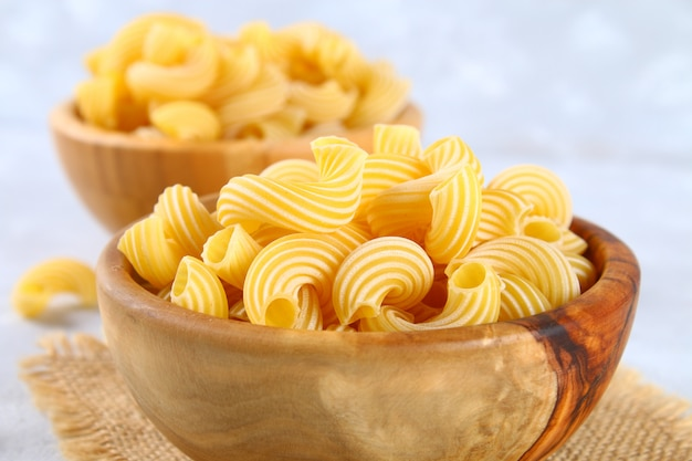 Raw pasta cavatappi or cellentani on a gray table