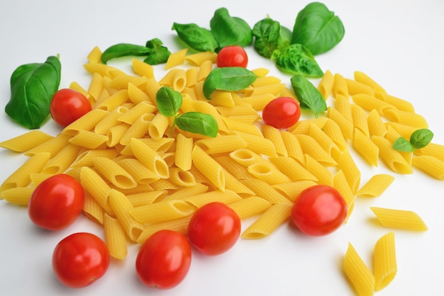 Raw pasta, cherry-tomatoes and basil on white background. ingredients for italian pasta. top view.