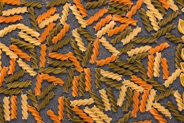 Raw pasta closeup. fusilli spaghetti pattern background. colorful fusilli