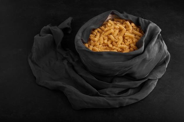 Pasta cruda in un contenitore avvolto con tovaglia blu.